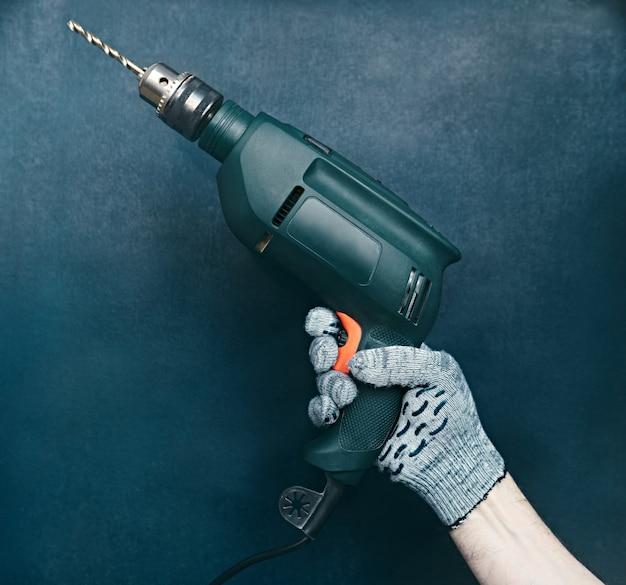 Зеленое сверло в руке строителя на синей поверхности