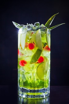 Коктейль зеленого напитка с яблоком, лаймом и вишней в большой банке для большой компании, крупным планом, изолированным на черном.