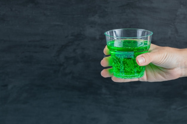 Green drink in the hand with water bubbles inside