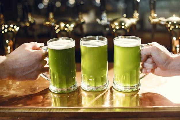 유리에 녹색 음료. 남자의 손에 유리. 바에서 맥주.