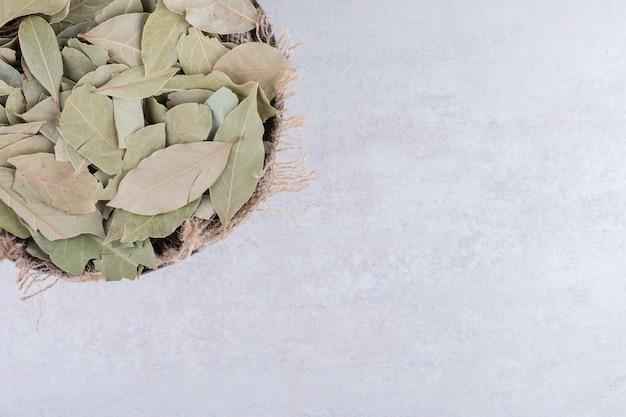 Foglie di alloro secche verdi in una tazza sulla superficie di cemento