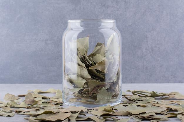 Зеленые сухие лавровые листья в чашке на бетонной поверхности