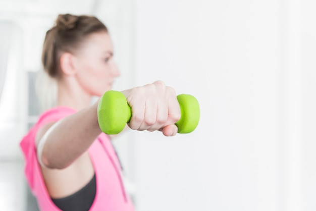Green dumbbell lifted by woman in sportswear