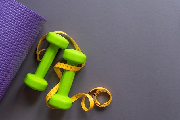 Зеленые гантели и гимнастический коврик на темно-сером бумажном фоне. ваш текст там. концепция спортивного образа жизни.