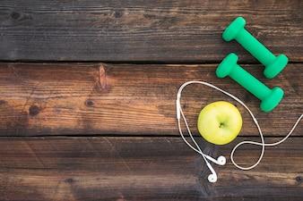Green dumbbells; apple and white earphone on wooden plank