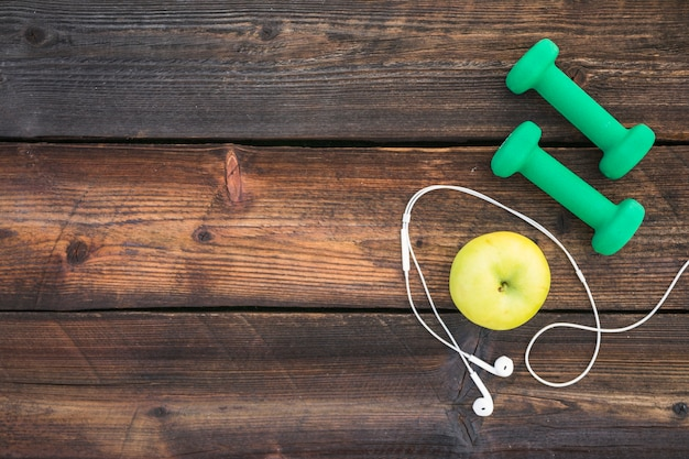 Green dumbbells; apple and white earphone on wooden plank