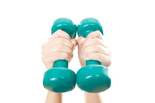 白で隔離の女性の手の緑のダンベル