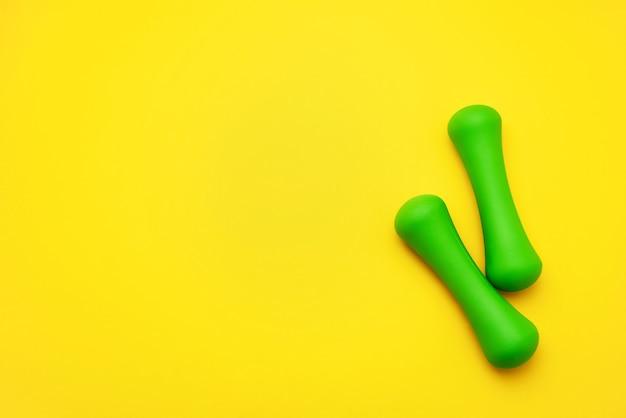 緑のダンベルは黄色の背景にあります。スポーツと健康的なライフスタイルの概念。コピースペース、上面図。