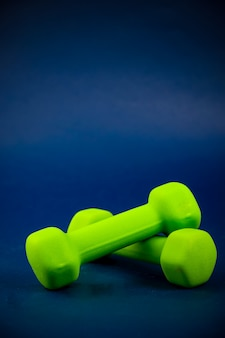 Green dumbbells lie on top of each other
