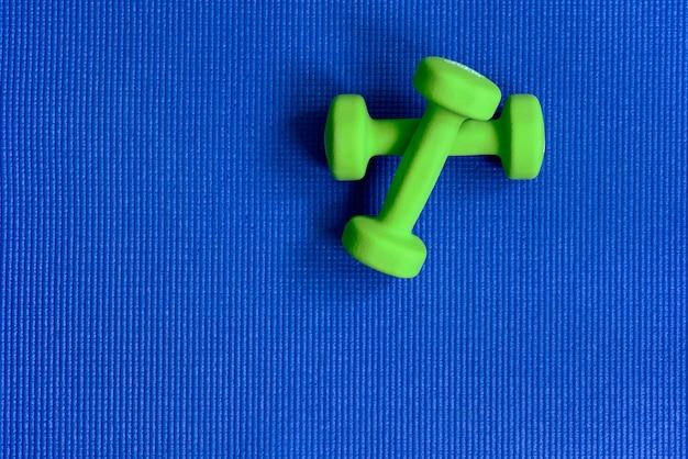 青いエクササイズマットの上の緑のダンベルは、アクティブな健康的なライフスタイルの概念を表示します