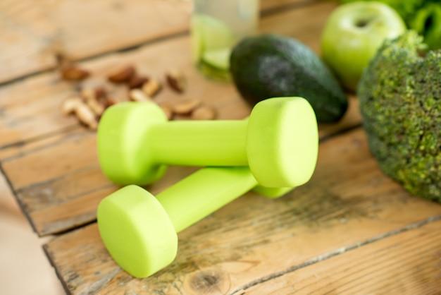 식탁에 건강한 음식이 있는 녹색 아령