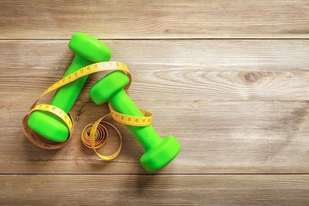 木製の背景に巻尺と緑のダンベル