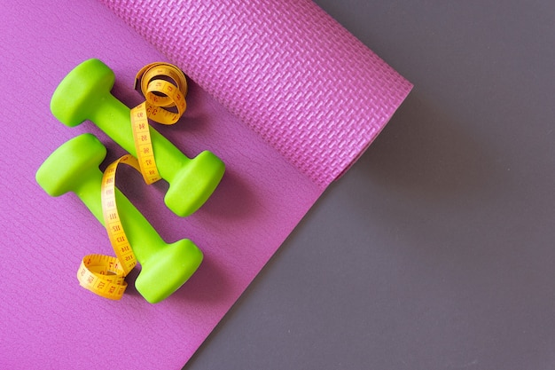 Green dumbbells with measuring tape on a red sports mat on a gray background. fitness concept and healthy lifestyle. copy space.