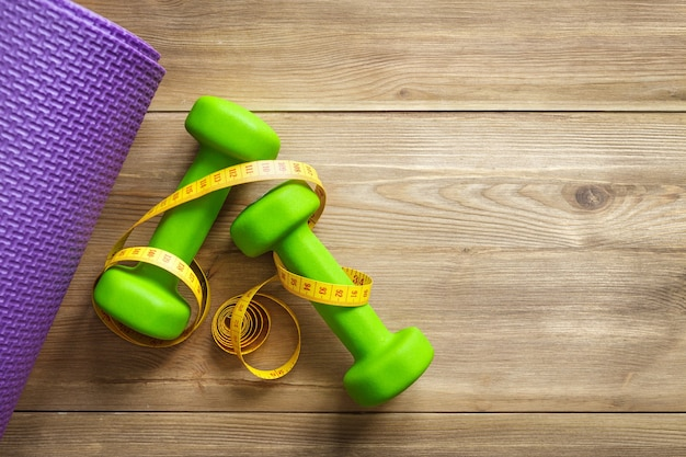 Green dumbbells with a sports mat on a wooden background. the concept of a healthy lifestyle, fitness, yoga.