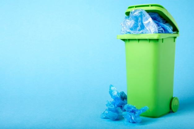 Green dustbin on a blue background. polyethylene. recycling.