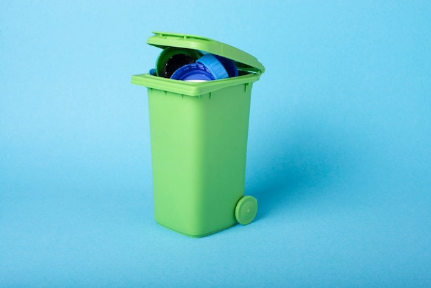 Green dustbin on a blue background with plastic waste. plastic recycling.