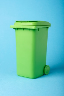 Green dustbin on a blue background.