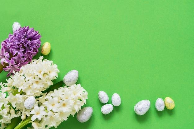 緑のイースターの背景。緑の背景に春の花と装飾的なイースターエッグ。コピースペース