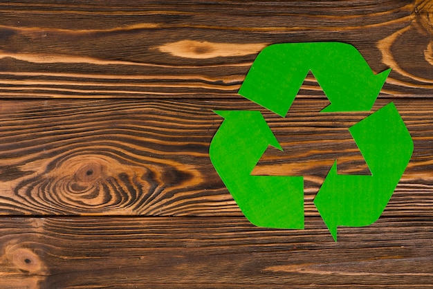 Green eco recycle logo on wooden background