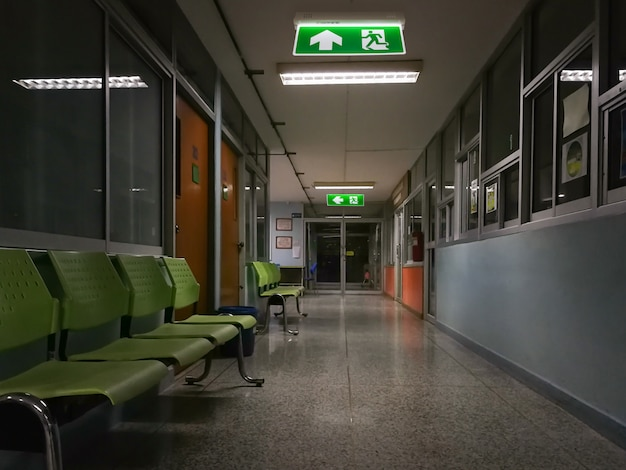 Green emergency exit sign in hospital showing the way to escape at night