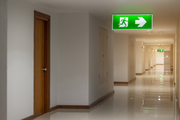 Green emergency exit sign in hotel showing the way to escape