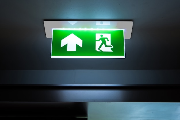 Green emergency exit sign showing the way to escape.