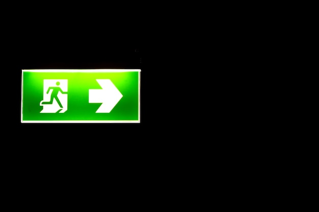 Green emergency exit sing in darkness.