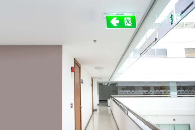 The green emergency fire escape sign on the ceiling