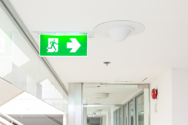 Green emergency fire exit sign or fire escape in the building.