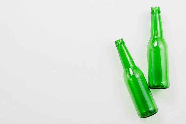 Green empty bottles on white background