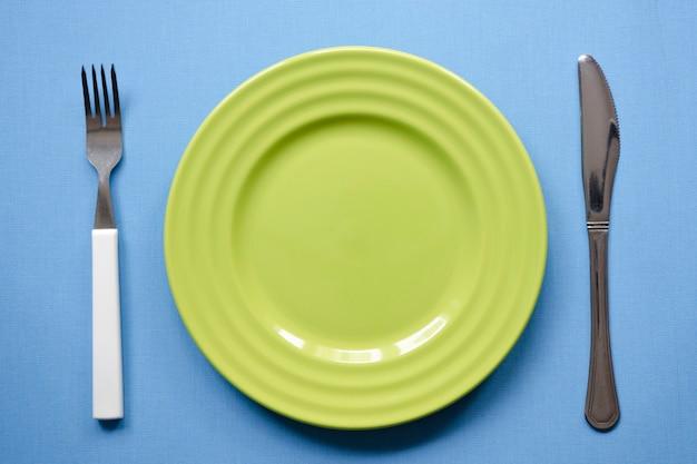 포크와 나이프가 있는 파란색 식탁보에 있는 녹색 빈 접시