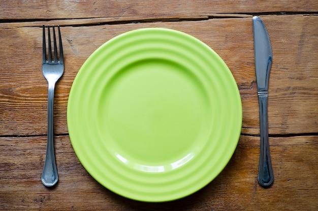 포크와 나이프가 있는 빈티지 나무 테이블에 있는 녹색 빈 접시