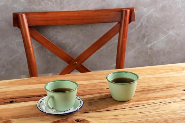 木製のテーブルの上の緑のエナメルカップ、伝統的な素朴なアフタヌーンティーのコンセプト。広告用のコピースペース