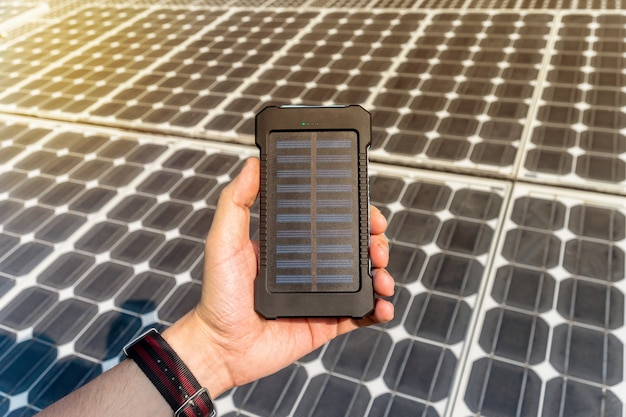 Зеленая энергия, фотоэлектрические солнечные батареи с рукой. мобильный power bank в руке на фоне больших солнечных батарей. зарядное устройство для телефона на солнечной энергии