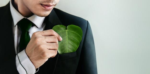グリーンエネルギー、再生可能で持続可能な資源。環境とエコロジーケアのコンセプト。ポケットにハート形の緑の葉を保持しているビジネスマンを閉じる