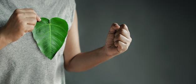 Зеленая энергия, возобновляемые и устойчивые ресурсы. концепция охраны окружающей среды и экологии. крупным планом руки, держащей зеленый лист в форме сердца