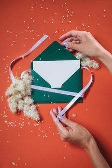 Green envelope in hands on an orange background. certificate