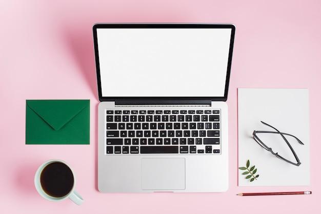 Зеленый конверт; чайная чашка; ноутбук; очки на бумаге и карандаш на розовом фоне