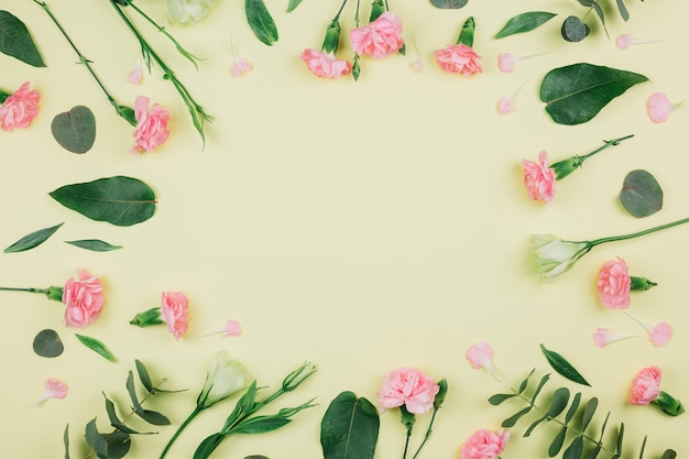 Green eucalyptus populus leaves; pink carnations and eustoma flowers with space in the center on yellow background