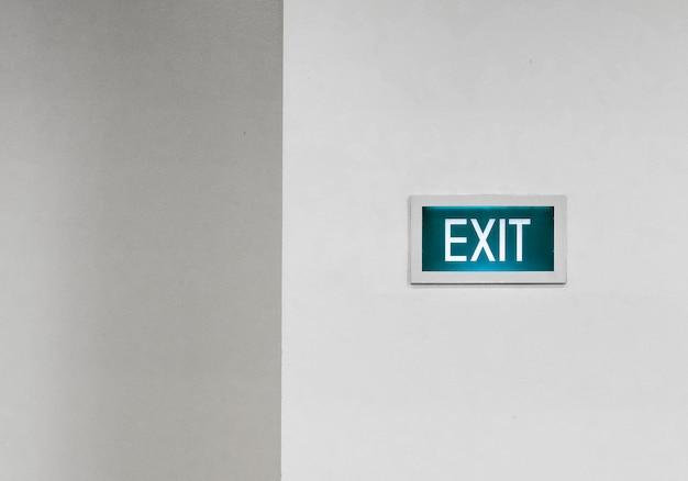 흰 벽에 녹색 출구 표시