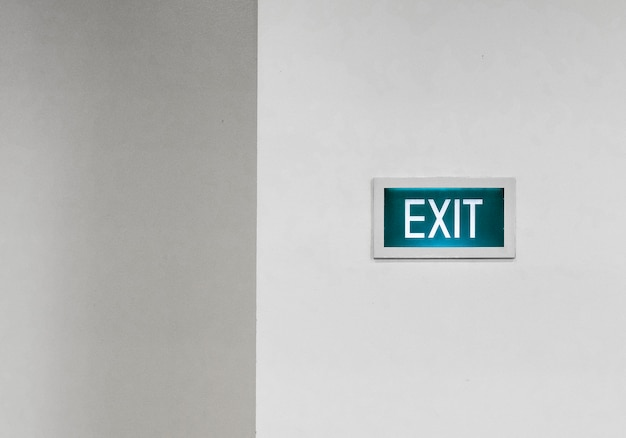 Green exit sign on a white wall