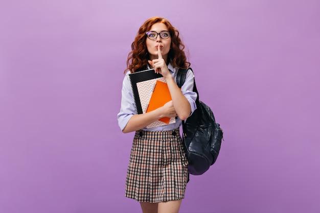 Green eyed girl in eyeglasses holds notebooks on purple wall