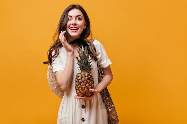 Ragazza dagli occhi verdi in vestito bianco che tiene ananas. la donna ride e posa con la borsa della spesa su sfondo arancione.
