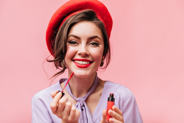 Зеленоглазая девушка с белоснежной улыбкой красит губы красной помадой. портрет дамы в стильном берете на розовом фоне.