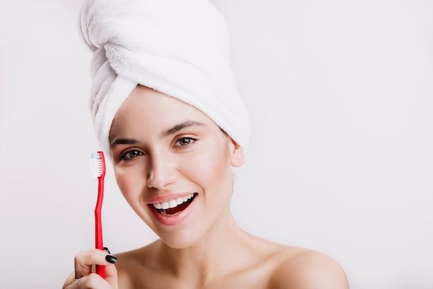 頭にタオルをかぶった緑色の目の女の子が笑っています。歯ブラシでポーズをとる化粧のない女性。