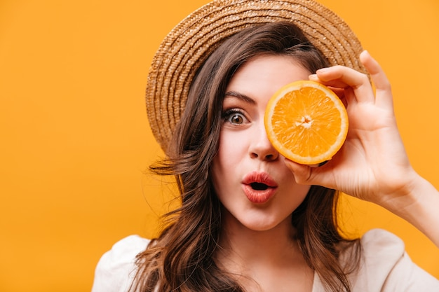 Green-eyed girl with wavy hair looks at camera in surprise and covers her eye with orange.