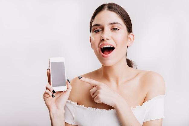 La ragazza dagli occhi verdi senza trucco dimostra il telefono sul muro bianco.