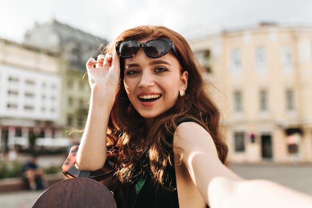 녹색 외 눈 박이 아가씨 선글라스를 벗고 셀카 촬영