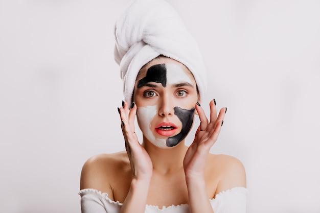 샤워 후 녹색 눈의 모델은 흰색과 검은 색 점토의 얼굴 마스크를 만듭니다. 그녀의 머리에 흰 수건을 가진 소녀