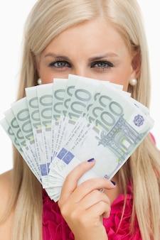 100ユーロの紙幣を持っている緑の目の女